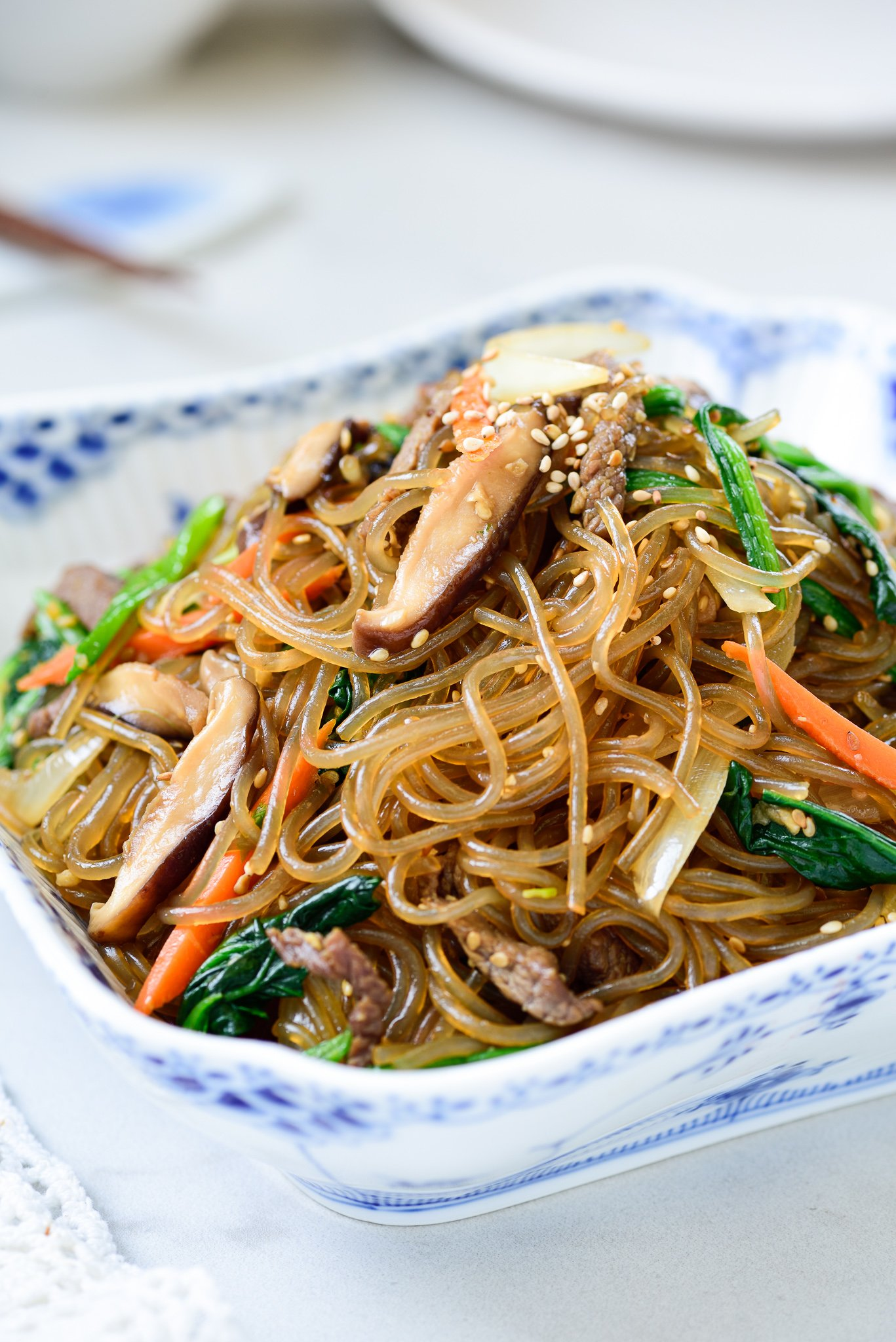 Stir-fried glass noodles with beef and vegetables in a square bowl