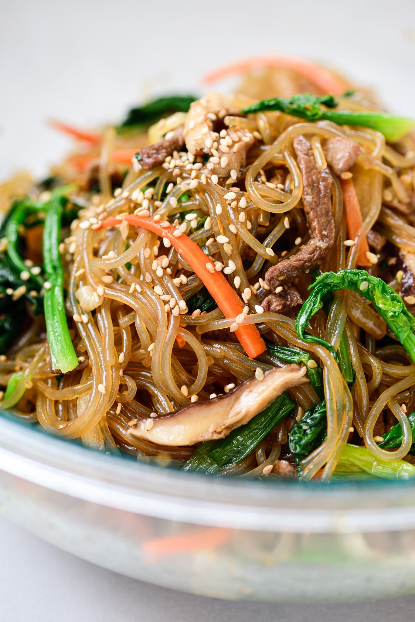 Stir-fried starch noodles with beef, spinach, carrot and mushroom strips in a big Pyrex bowl