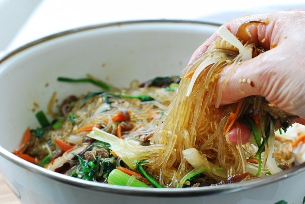 Mixing japchae noodles with beef and vegetables