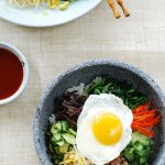 Korean rice bowl with beef, vegetables and egg in a stone pot