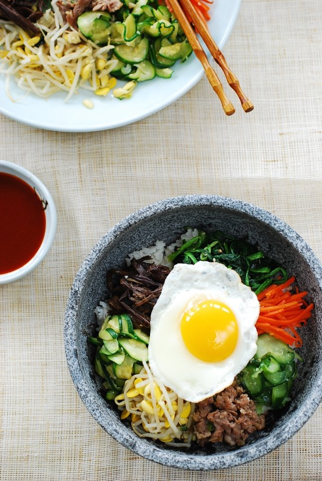 overhead shot of Korean Bibimbap Bowls with Beef, Vegetables and a fried egg served in a Korean Stone Bowl with a small dish of bibimbap sauce on the side - bibimbap recioe
