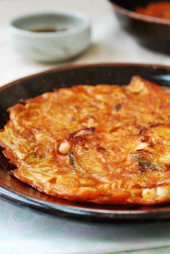 Close-up of a Korean kimchi pancake (kimchijeon) served on a black plate with pancake dipping sauce in the background
