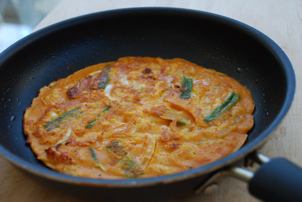 kimchijeon cripsy kimchi pancake being fried in a small black pan