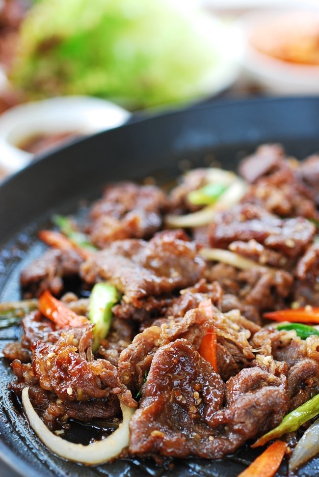 Close-up of caramelized pieced of Korean BBQ Beef with crisp veggies in a black skillet