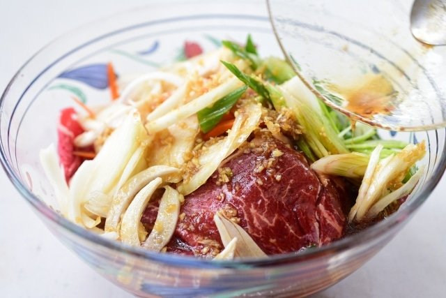 thinly sliced beef and vegetables being mixed with the marinade