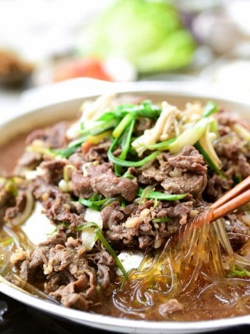 Korean BBQ beef cooked in a pan with broth and noodles