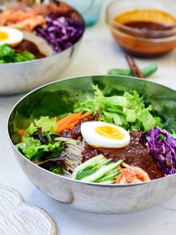 Cold noodles with colorful vegetables and a spicy gochujang sauce with a half boiled egg on top