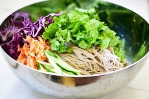 arranging julienned vegetables on top of buckwheat noodles