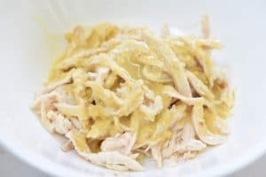 Mixing shredded chicken with pine nut dressing