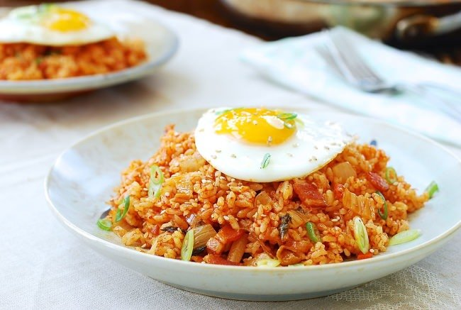 the best Korean Kimchi Fried Rice (kimchi bokkeumbap) served in a white bowl with a fried egg on top