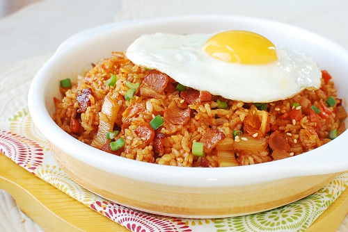 side view of a bowl of Korean Kimchi Fried Rice with bacon served the traditional way, with a fried egg on top
