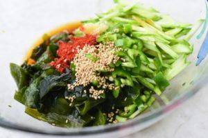 cucumbers and seaweed being seasoned in a bowl