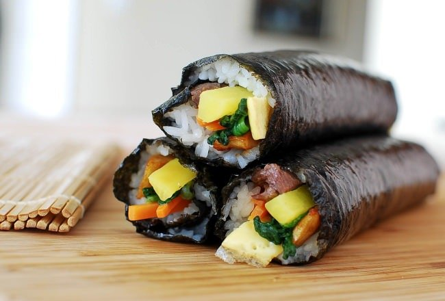 three gimpab rolls (Korean sushi rolls) with seasoned burdock, veggies and eggs, stacked on top of each other
