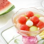 a Korean punch drink with watermelon and rice cake balls in a glass bowl