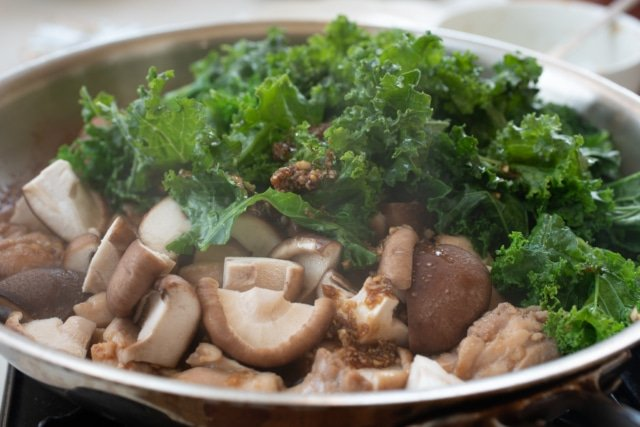 Kale and mushrooms being stir fried with chicken