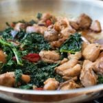 Stir frying chicken, kale and mushrooms in a pan