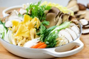 arranging an assortment of mushrooms and other vegetables for Korean hot pot