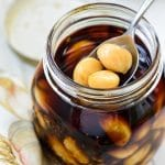 Soy pickled garlic cloves in a mason jar with a spoon holding a few in the jar