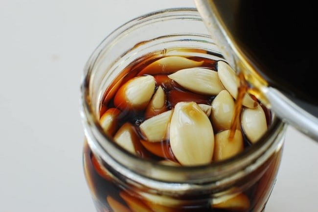 Korean pickled garlic in a jar with a soy brine