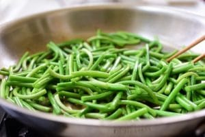 stir-frying garlic scapes in a pan
