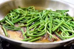 stir-frying garlic scapes in a sauce