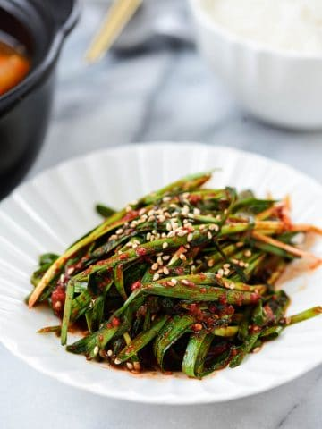 Korean garlic chive kimchi in a small plate served with a bowl of rice