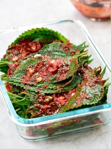 Red spicy perilla leaf kimchi in a pyrex container