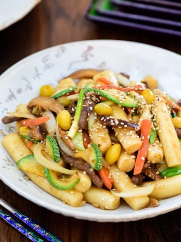 Korean finger size rice cakes stir-fried with beef, mushrooms, carrot, zucchini slices