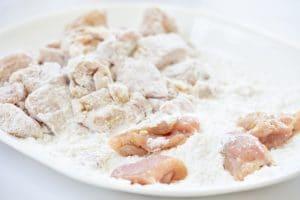 Dredging chicken pieces in starch