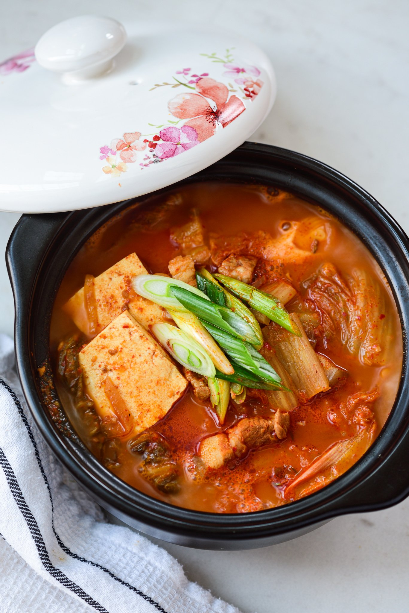 kimchi stew with tofu in an earthen pot with the lid laid on the side of the pot