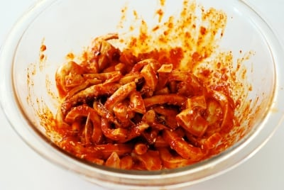 squid being mixed with a red spicy sauce
