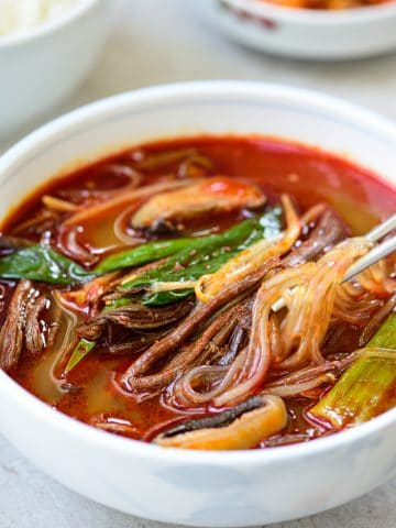 Korean red spicy soup with shredded beef, scallions, mushrooms and noodles in a large bowl