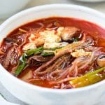 Korean red spicy soup with shredded beef, scallions, mushrooms eggs and noodles in a large bowl