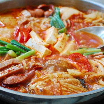 korean spicy stew with kimchi, spam, bacon, hot dogs, and tofu
