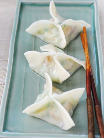 three boiled zucchini dumplings in square or star shape on a green rectangle shape plate