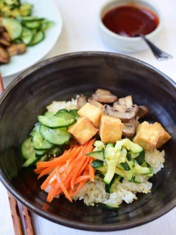 Tofu bibimbap in a large bowl with gochujang sauce