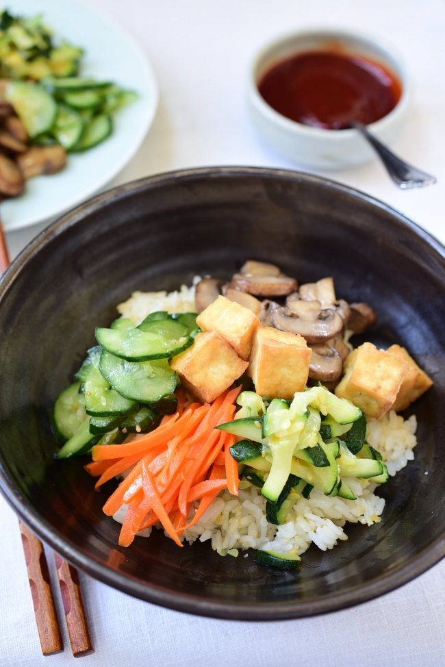 Tofu bibimbap in a large bowl with gochujang sauce