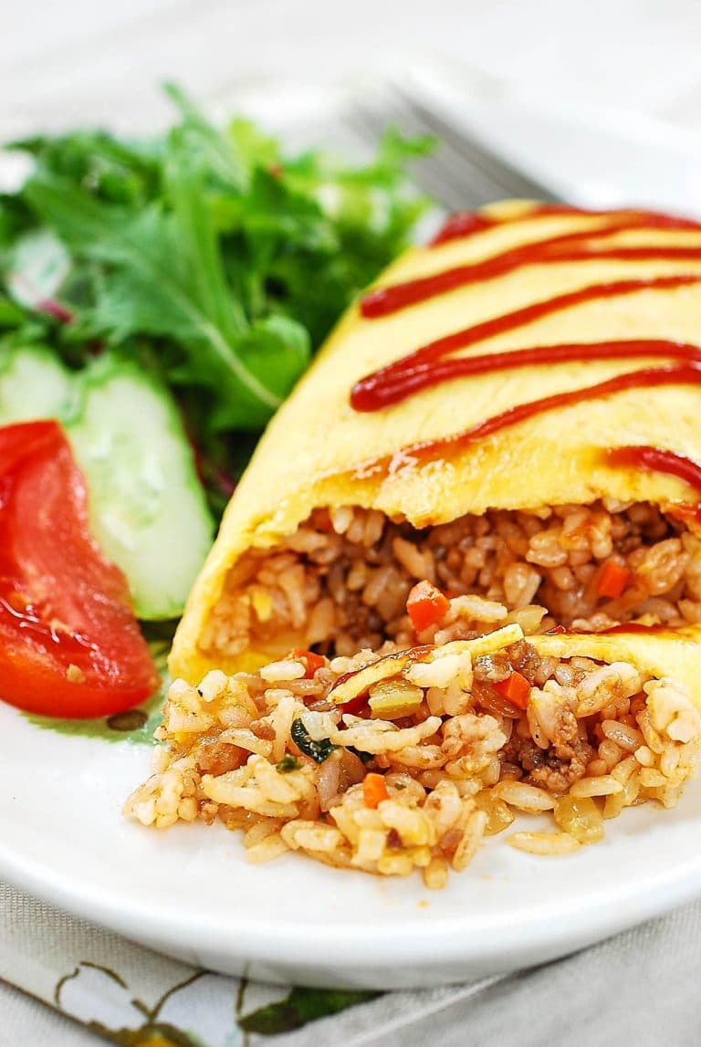 Fried rice wrapped in egg omelette drizzled with ketchup and served with lettuce, cucumber and tomato pieces