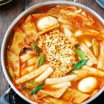 Korean spicy rice cakes with fish cake, boiled eggs and ramen noodles in the middle in a shallow pot
