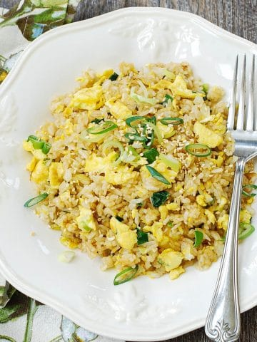 Egg fried rice with scallions in a white plate with a fork