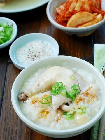 Chicken leg on top of rice porridge served with kimchi
