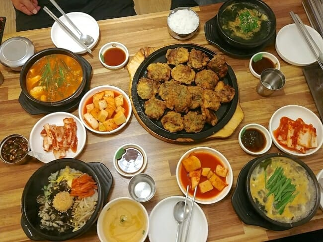 an array of Korean oyster dishes at a restaurant in Korea
