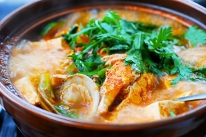 Korean spicy fish stew with clams, tofu and green veggies in an earthenware