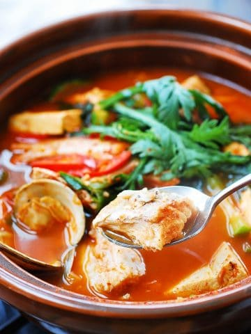 Korean spicy fish stew with clams, tofu and green veggies in an earthenware with a fish piece in a spoon