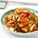 Cucumber kimchi in a plate with chopsticks in the background