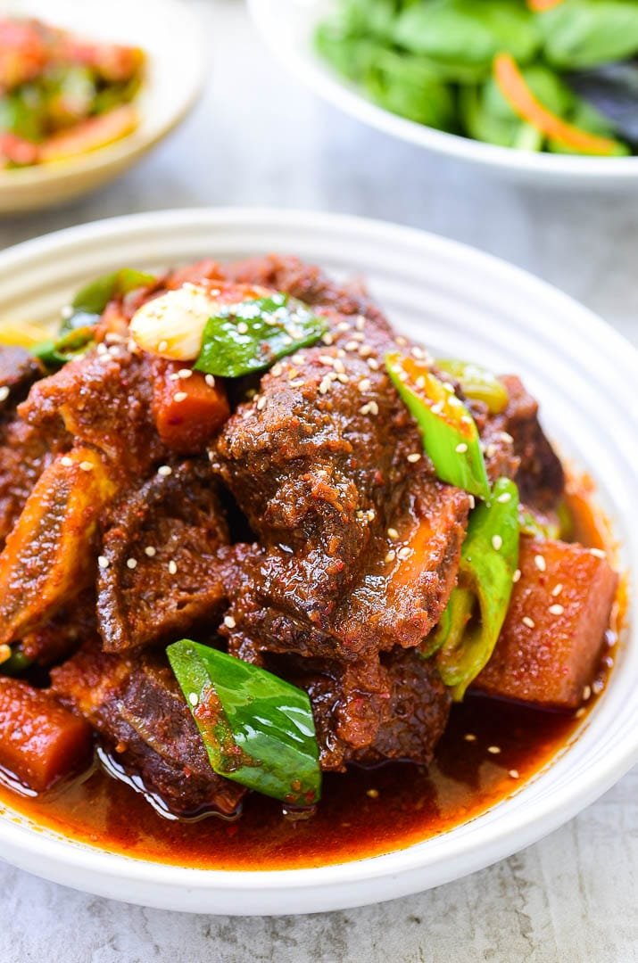 Red spicy braised short ribs with vegetables in a white plate
