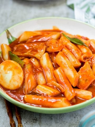 Red spicy Korean rice cake called tteokbokki in a large plate
