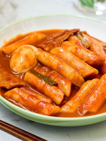Red spicy stir-fried finger shaped Korean rice cakes with a boiled egg