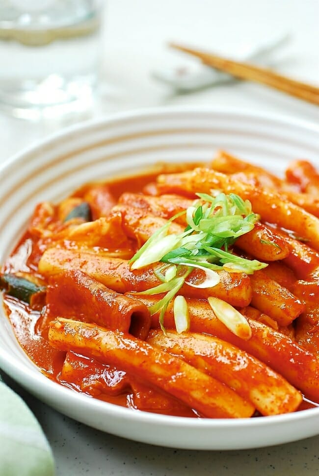 Korean stir-fried long cylinder shape rice cakes in a red spicy sauce