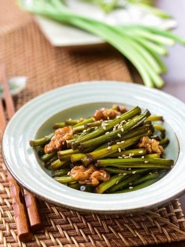 Garlic scapes stir-fried with walnuts and served in a small bowl as a side dish